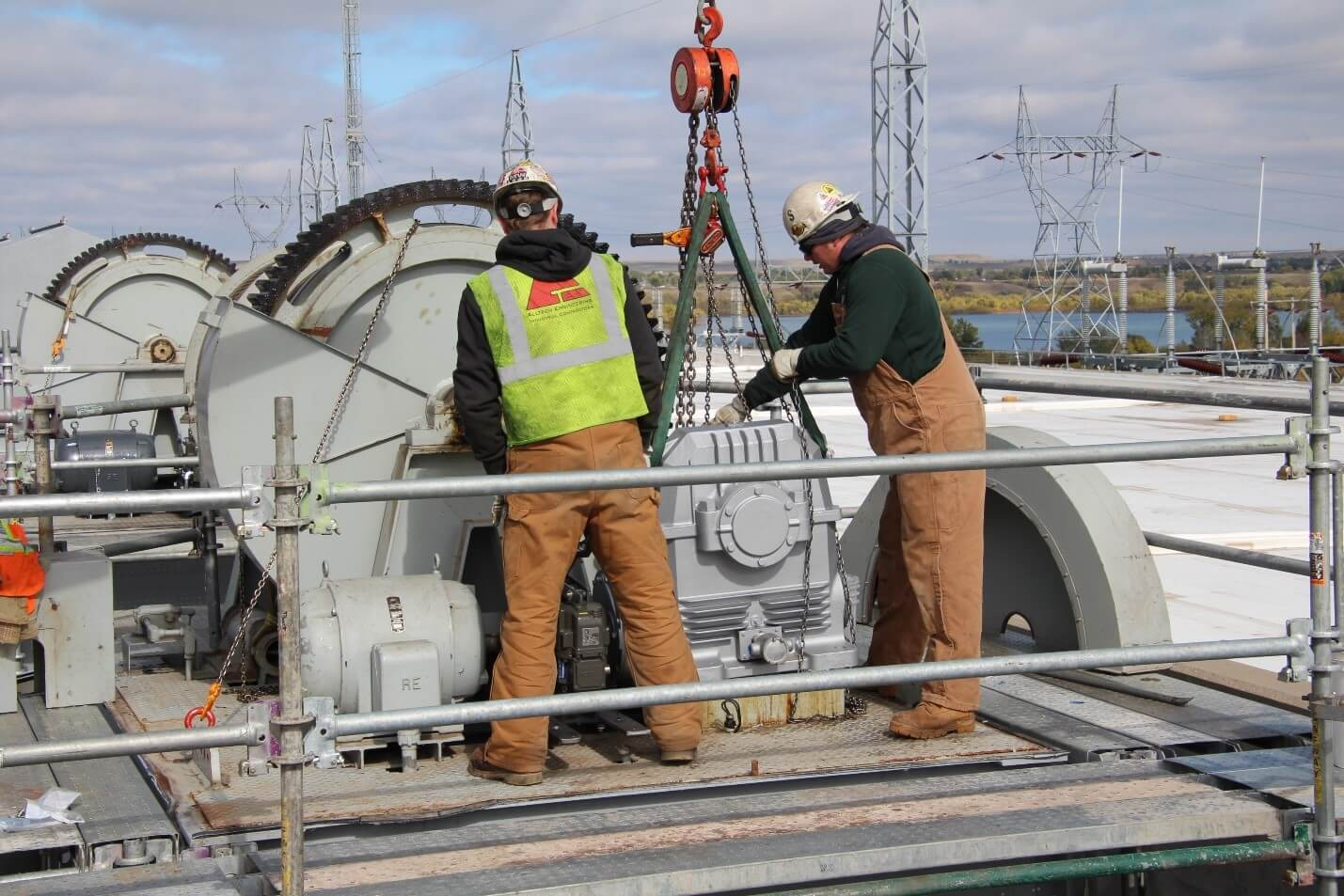 Two men standing while working on Big Bend Gearbox