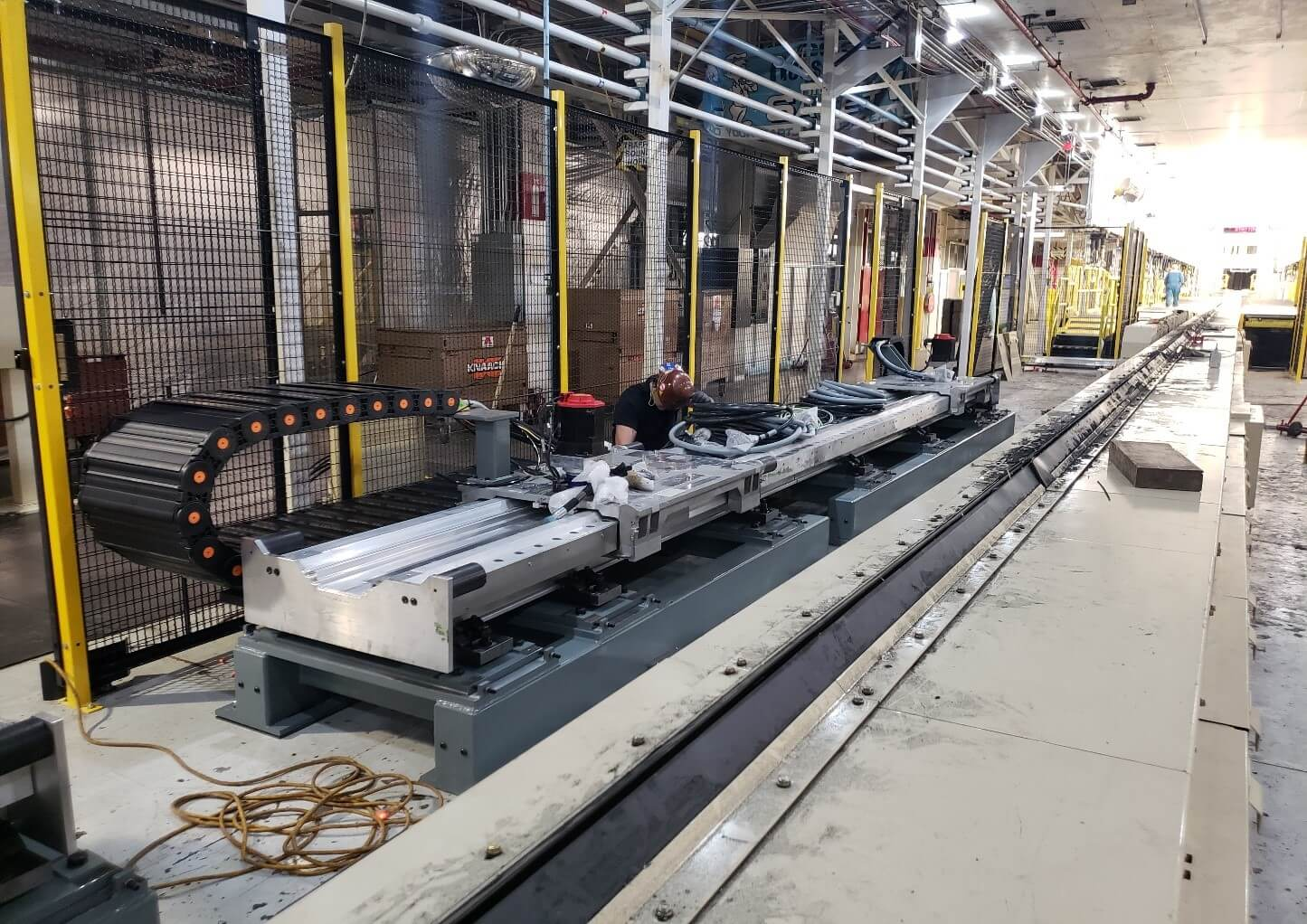 Person Working on the New Robotic Sealer Cell Installation